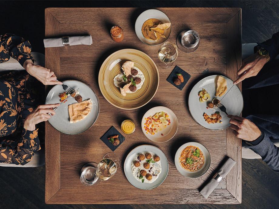 food-sharing-dinner-tisch-von-oben-paar-beim-essen-ifen-hotel_920x690